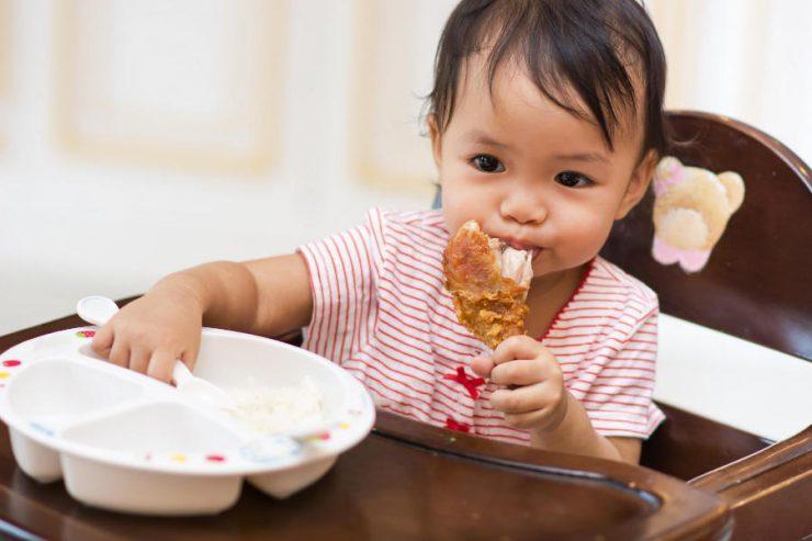 bimba che mangia pollo