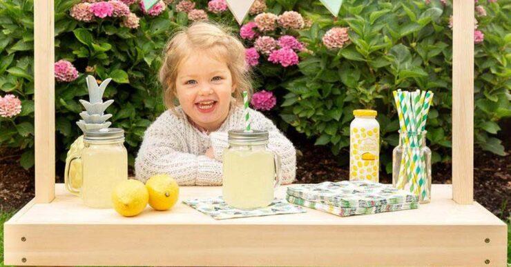 Bambina con chiosco per limonata