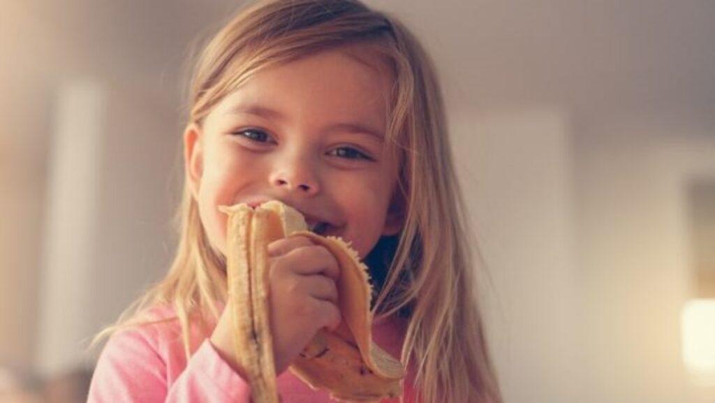 Bambina che mangia la banana